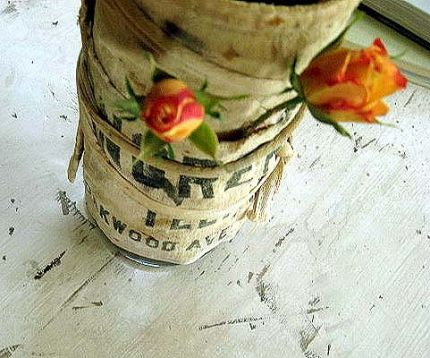 To add a little extra shabbiness , an old carpenters apron is wrapped around a glass vase.